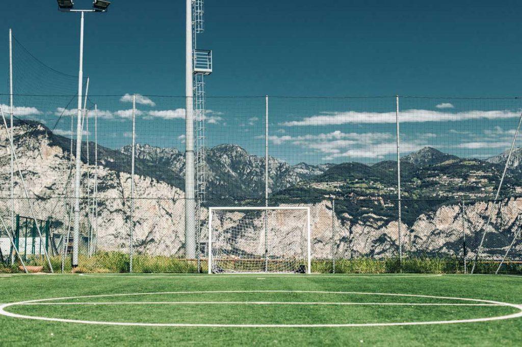 Boisko piłkarskie - widok na bramkę otoczoną piłkochwytami. W tle widać góry oraz błękitne niebo.